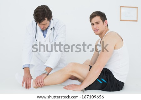 Side view of a young man getting his ankle examined at the medical office