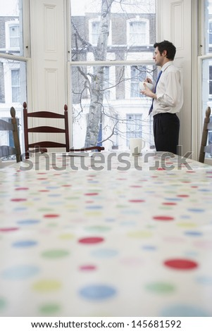 Side view of a young man in formals standing at window in dining room - stock photo