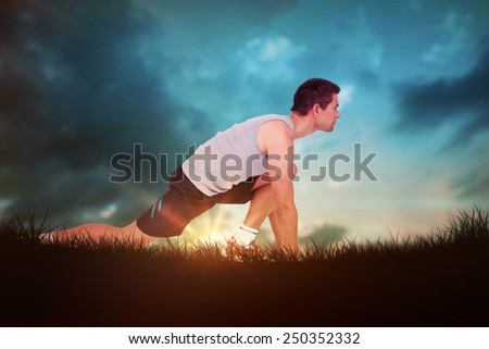 Side view of a young man in ready to run posture against blue sky over grass - stock photo