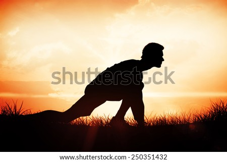 Side view of a young man in ready to run posture against orange sunrise - stock photo