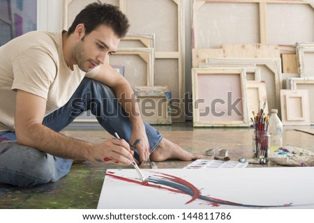 Side view of a young man painting on canvas on studio floor - stock photo
