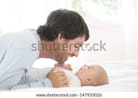 Side view of a young man playing with his little baby in bed - stock photo