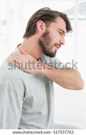 Side view of a young man suffering from shoulder pain in the medical office