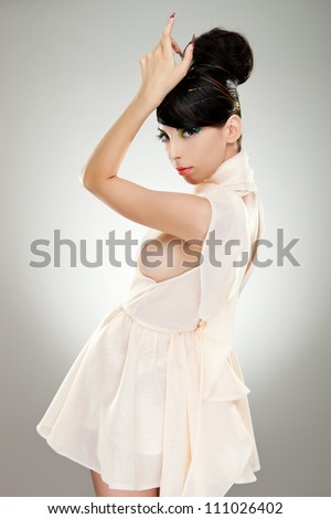 Side view of a young woman model in beautiful white dress looking at the camera. She is holding her arm raised revealing her breast - stock photo