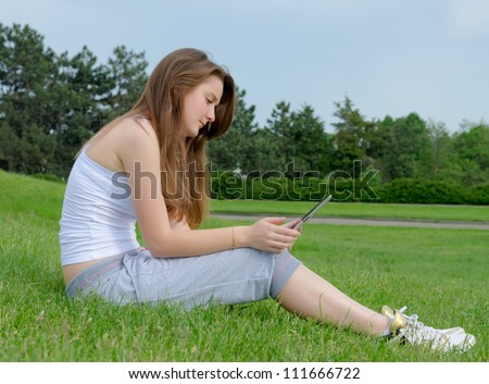 Side view of a young woman sitting in green grass working on a touchscreen tablet in the park