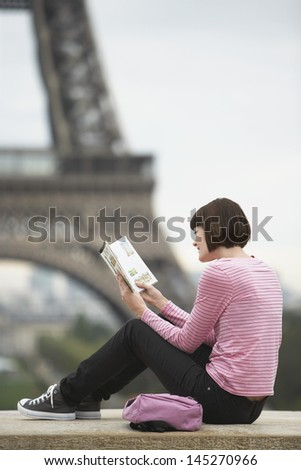 Side view of a young woman sitting on balcony and reading book in front of Eiffel Tower - stock photo