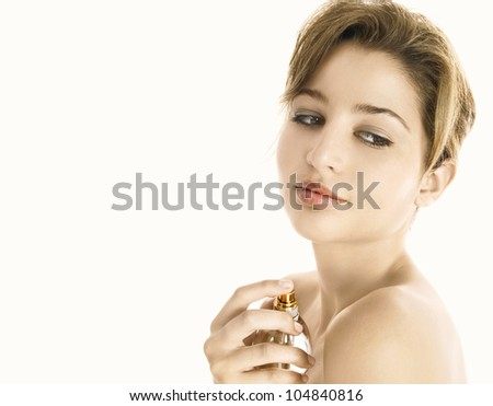 Side view of a young woman spraying perfume on her bare shoulders, smiling.