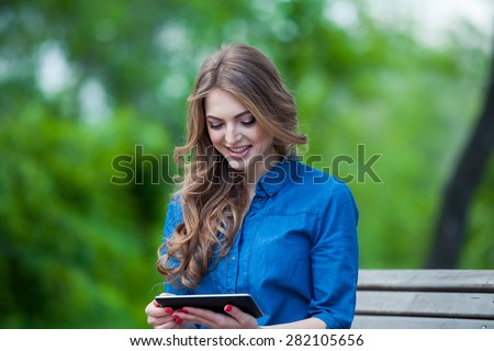 Side view of a young woman using a tablet computer on a park bench