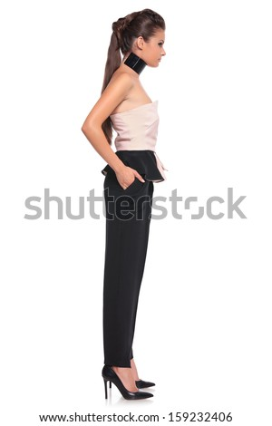 side view of a young woman with hands in her pockets on white background - stock photo