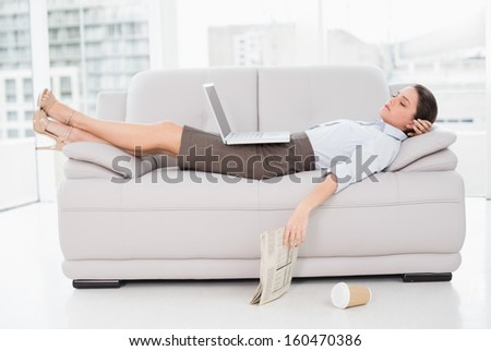 Side view of a young woman with laptop sleeping on sofa at home - stock photo