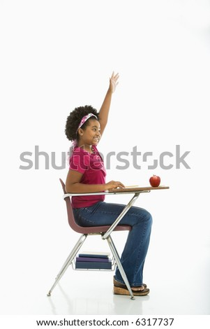 Side view of African American girl sitting in school desk raising hand.