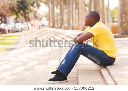 side view of african man relaxing in urban city - stock photo