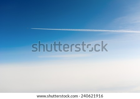 Side view of airplane contrail passing by against clear blue sky with sun flare - stock photo