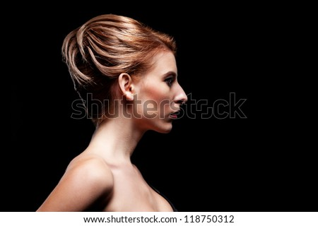 side-view of alluring model with hairstyle over black background - stock photo