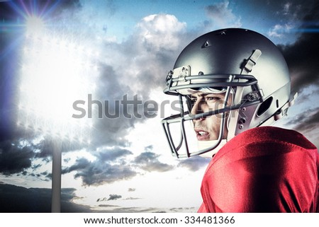 Side view of American football player looking away against spotlight in sky