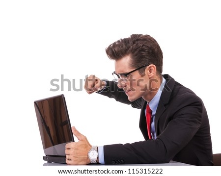 side view of an angry business man at his laptop, on gray background - stock photo