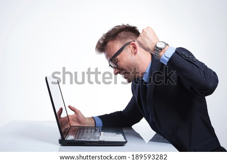 side view of an angry young business man wanting to punch his laptop. on a gray studio backgroud - stock photo
