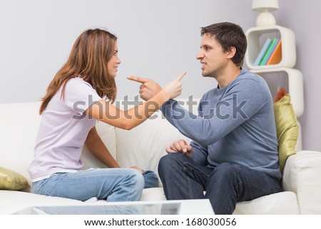 Side view of an angry young couple having an argument in their living room at home - stock photo