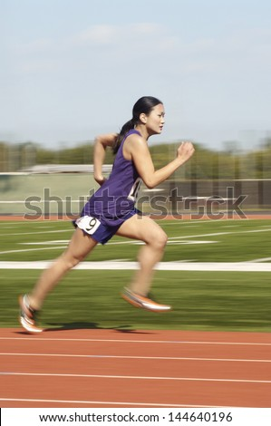Side view of an Asian female athlete running on race track - stock photo