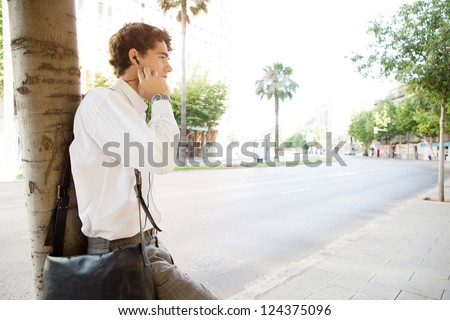 Side view of an attractive businessman leaning on a tree trunk by a large city avenue street, using his headphones to have a phone conversation. - stock photo