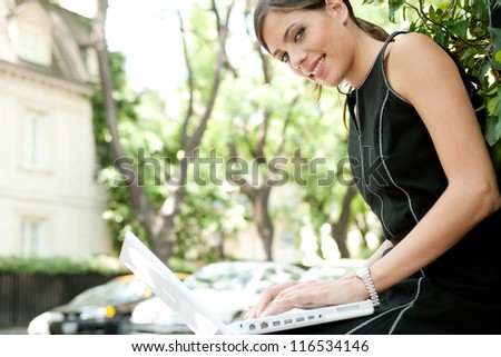 Side view of an attractive businesswoman using a laptop computer while sitting in a leafy city street during a sunny day, smiling. - stock photo