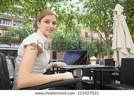 Side view of an attractive young professional business woman sitting at a cafe terrace shop drinking coffee and using a laptop computer in the financial district of a financial city, outdoors.