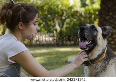 Side view of an attractive young woman petting her dog, an adult German Pinscher wearing a collar who is panting happily with its tongue hanging out - stock photo