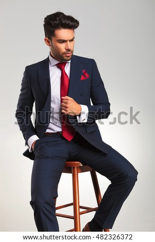 side view of an elegant business man holding his coat and looks away from the camera while sitting on a stool