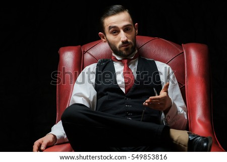 side view of an elegant young businessman smoking a cigarette on black studio background
