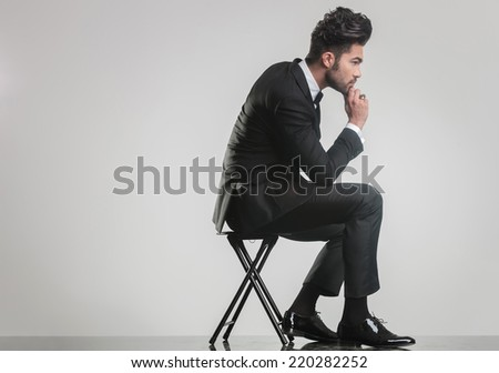 Side view of an elegant young man sitting on a stool and thinking while holding one hand to his chin.  - stock photo