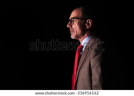 side view of an old business man looking away from the camera on black studio background - stock photo
