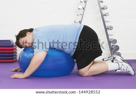Side view of an overweight man sleeping on exercise ball in health club - stock photo