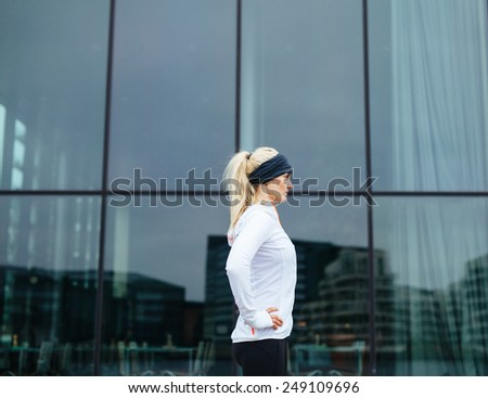Side view of an sporty young female ready for her outdoor training session. Fitness woman standing outdoors with her hands in hips looking away. - stock photo