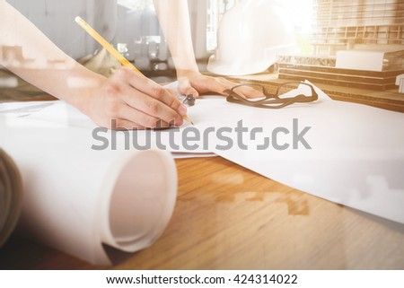 Side view of Architect hands sketching a construction project with calculator at work place. Vintage tone. - stock photo