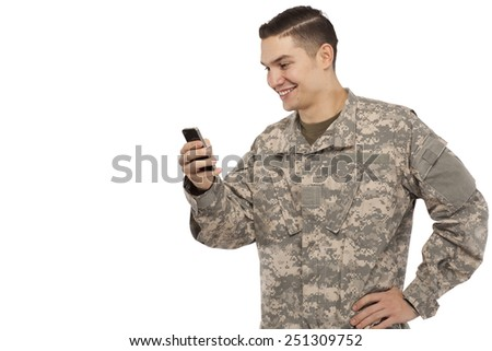 Side view of army soldier text messaging against white background - stock photo