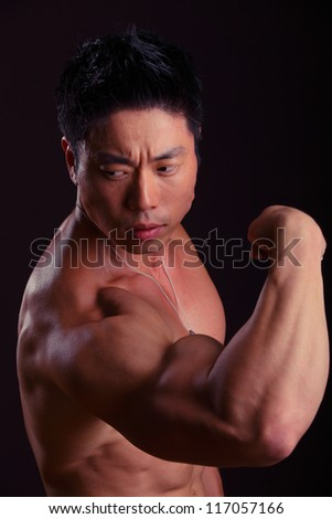 Side view of Asian Body Builder flexing bicep on black background - stock photo