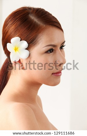 side view of asian woman with frangipani in her ear - stock photo