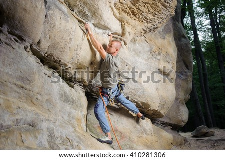Side view of athletic male lead climber climbing big boulder in nature. Man is searching for the next grip. Summer time. - stock photo