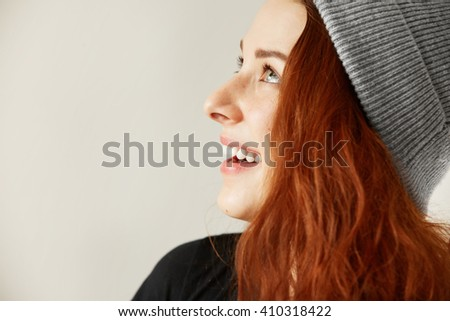 Side view of attractive happy young freckled female with long loose coppery hair in gray cap looking up with beautiful toothy smile. Positive human face expressions and emotions. Selective focus  - stock photo