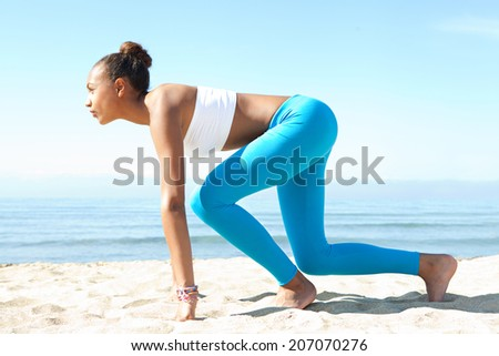 Side view of attractive healthy young african american woman crouching in the ready position to start running exercise training against a blue sea and sky during a sunny day. Sport lifestyle outdoors. - stock photo