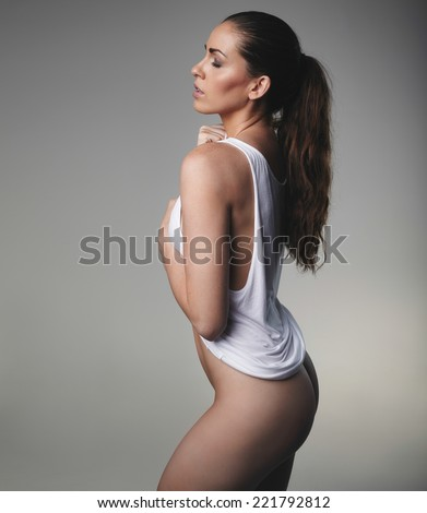 Side view of attractive woman wearing only a tank top on grey background. Female model posing seductively. - stock photo
