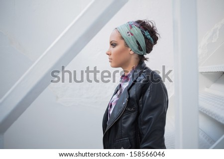 Side view of attractive woman with hairband sitting on stairs - stock photo