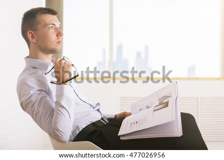 Side view of attractive young businessman sitting on chair, holding document and glasses in bright white brick room