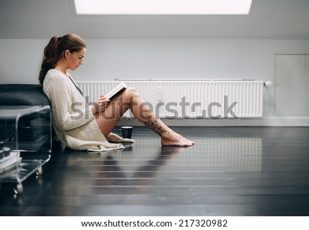 Side view of attractive young woman sitting on floor reading book. Caucasian female model at home reading a novel. - stock photo