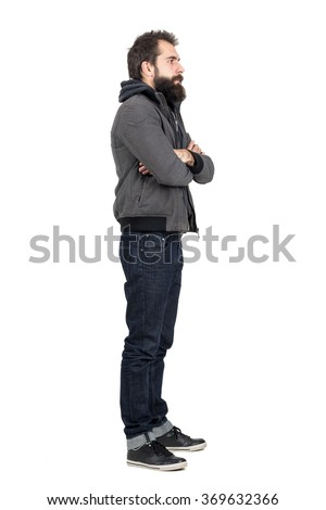 Side view of bearded man wearing jacket over hooded sweatshirt with crossed arms looking away. Full body length portrait isolated over white studio background.  - stock photo