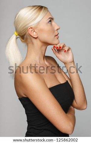 Side view of beautiful blond pensive woman with hand on chin, looking up over gray background