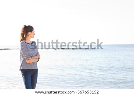Side view of beautiful healthy serene woman relaxing contemplating the sea on a beach destination, breathing fresh air, outdoors. Wellness, health and well being lifestyle. Recreation sunny exterior.