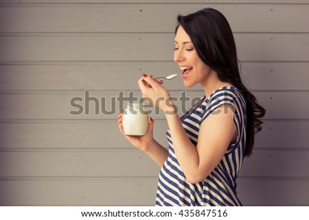 Side view of beautiful pregnant woman eating yogurt and smiling, standing against gray wall - stock photo