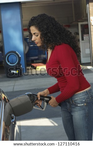 Side view of beautiful woman inserting nozzle in a car tank - stock photo