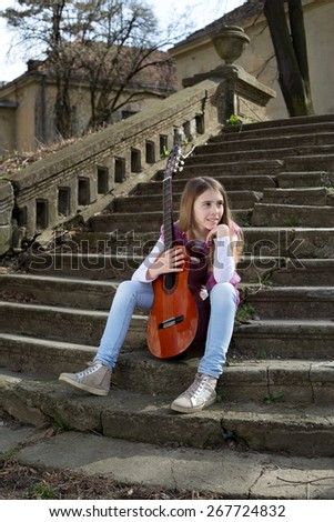 Side View of Beautiful Young Girl With Guitar in Front of Her Sitting on the Foot of the Stairs and Looking Thoughtfully at the Horizon - stock photo